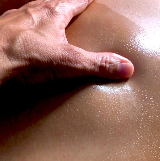 A hand massaging a back